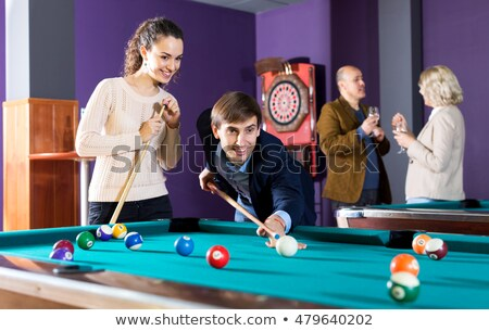 Young and mature couple playing billiard Stock photo © Kzenon