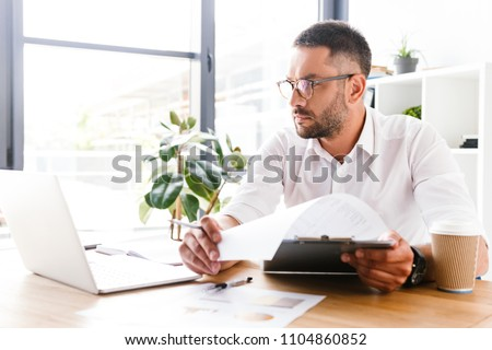 Portrait of concentrated smart businesslike man 30s in white shi Stock photo © deandrobot