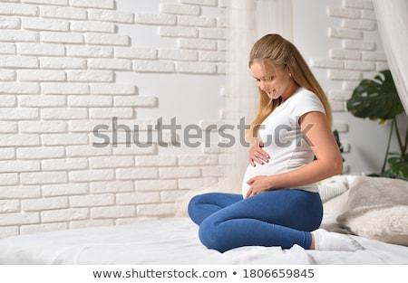 Gyönyörű terhes fiatal anya ül ágy Stock fotó © Lopolo