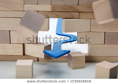 Arrow Breaking Through Wall Made Of Wooden Blocks Stock photo © AndreyPopov