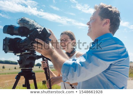 Cameraman with his camera and assistant working in production Stock photo © Kzenon