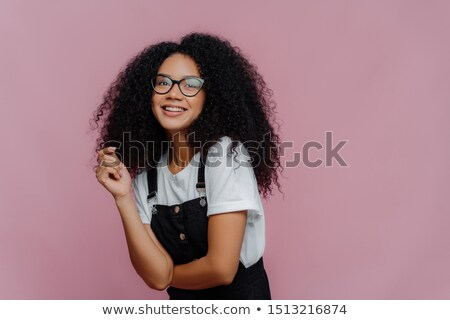 Studio shot of happy dark skinned lady with crisp hair, has dreamy expression, wears optical glasses Stock photo © vkstudio