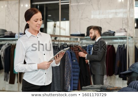 Pretty brunette shop assistant looking at tablet display on background of buyer Stock photo © pressmaster