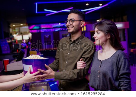 Happy young affectionate couple buying popcorn and tickets in cinema Stock photo © pressmaster