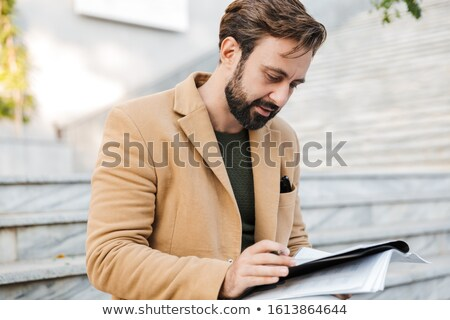 Image of handsome man woking with paper documents on stairs outd Stock photo © deandrobot