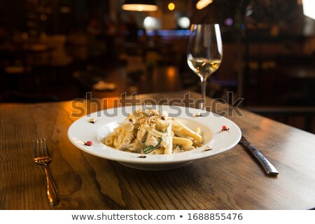 Penne with chicken, spinach and hazelnut in parmesan sauce Stock photo © boggy