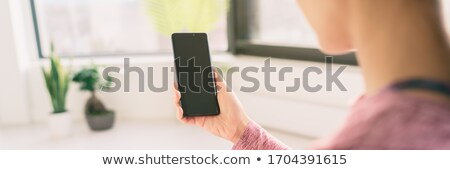 Woman using mobile phone staying home watching videos online on 5g data app view from behind holding Stock photo © Maridav