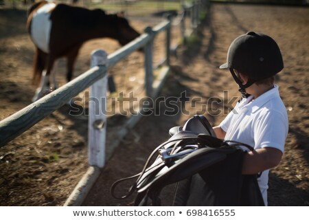 Boy carrying a saddle Stock photo © lovleah