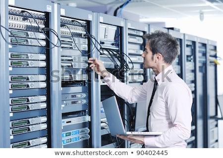 Businessman With Laptop In Network Server Room Сток-фото © dotshock