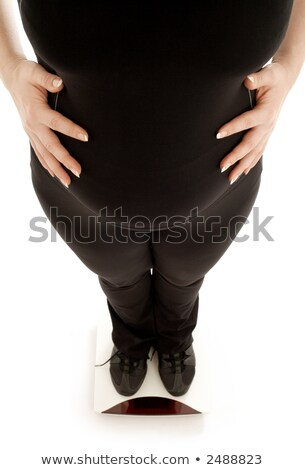 pregnant lady weighing oneself, focus on belly Stock photo © dolgachov