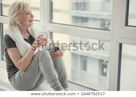 Elderly woman drinking bottled water at a gym stock photo © photography33