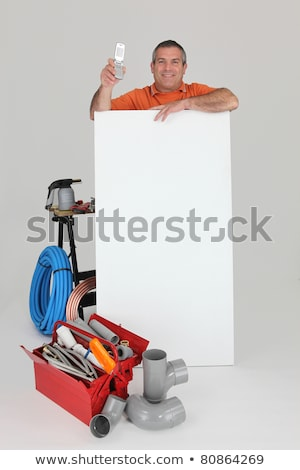 plumber behind wall showing phone stock photo © photography33