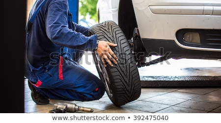 Stock photo: Changing a tire in a garage