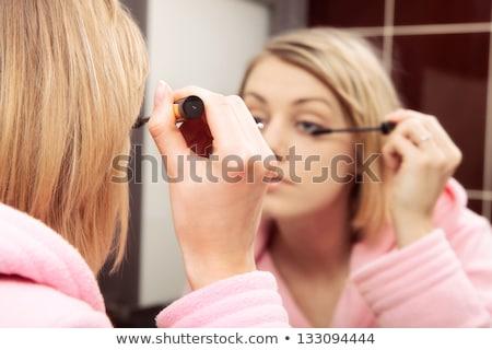 Blond woman in bathrobe holding mascara brush stock photo © photography33