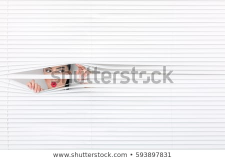 Woman peeking through blinds Stock photo © photography33