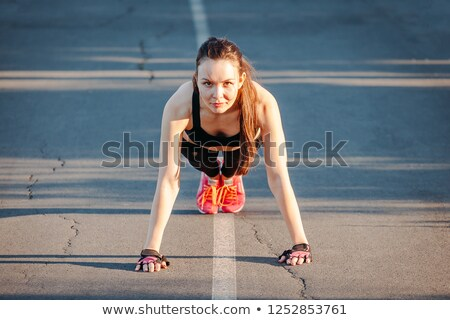 Portrait of happy young woman doing push-ups stock photo © wavebreak_media