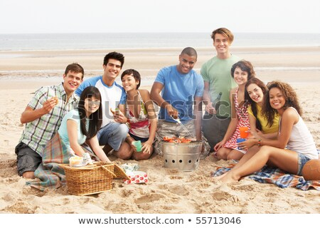 teenage couple enjoying barbeque on beach together stock photo © monkey_business