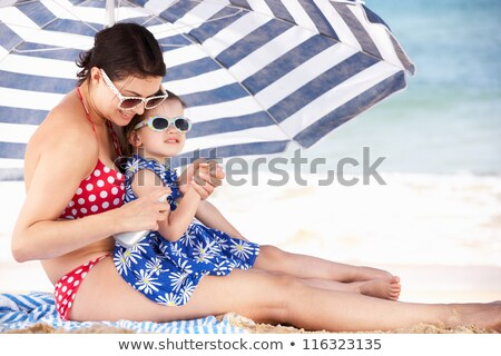 Two Women Sheltering From Sun On Beach Holiday Stock photo © monkey_business