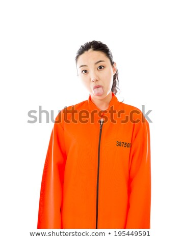 Young Asian woman sticking out her tongue in prisoners uniform Stock photo © bmonteny