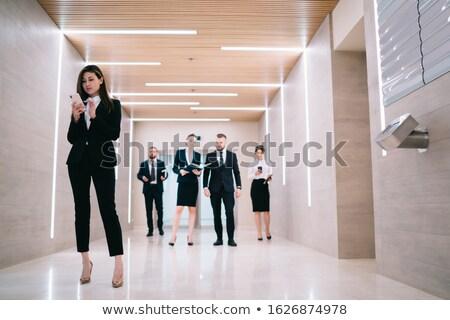 Businesswoman using smartphone in elevator Stock photo © deandrobot