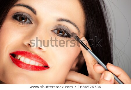 Cute brunette applying mascara or eyeliner stock photo © Morphart