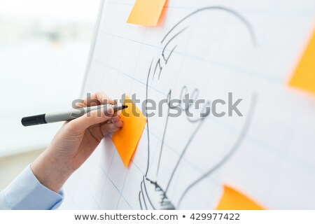 Photo stock: Close Up Of Hand Drawing Light Bulb On Flip Chart
