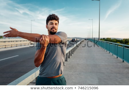 Handsome young muscular man stretching his arms Stock photo © deandrobot