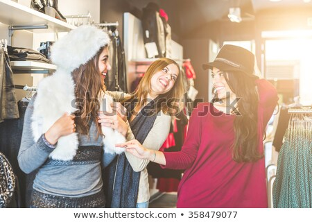 Stockfoto: Young Woman Shopping In A Fashion Store Trying On Some Clothes