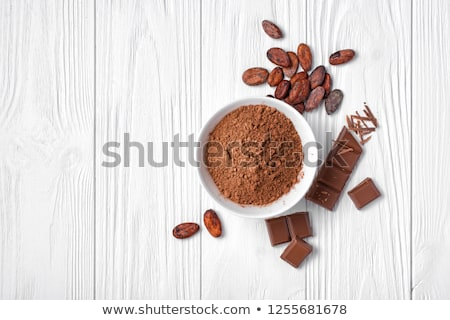 cocoa beans and powder on dark background top view copy space flat lay stock photo © yelenayemchuk