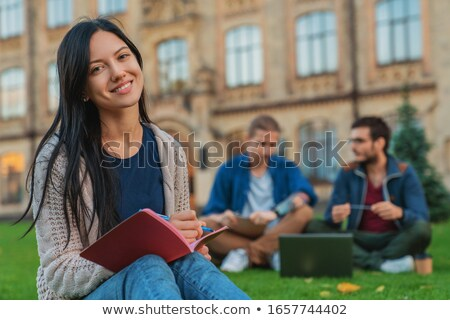 smiling young two women sitting outdoors in park writing notes stock photo © deandrobot
