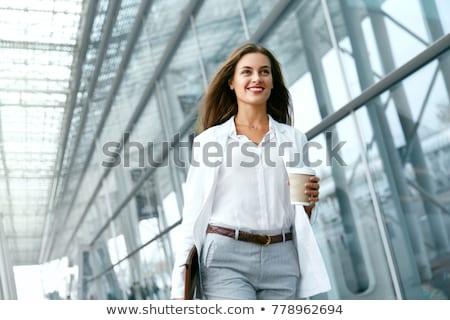 Beautiful young caucasian woman walking outdoors drinking coffee. Stock photo © deandrobot