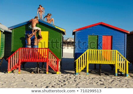 Group climbing up on top of beach hut Stock photo © IS2