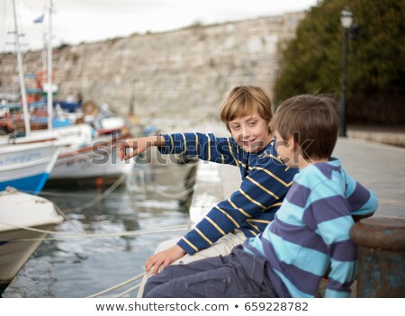 Boys in harbour, older one pointing Stock photo © IS2