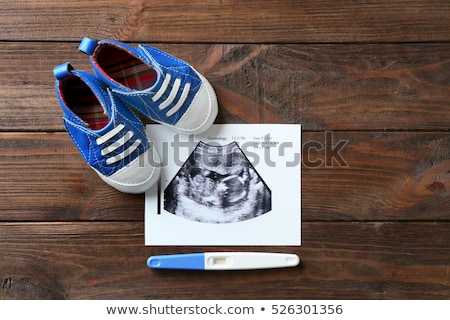 Pregnant woman examining baby shoes Stock photo © IS2