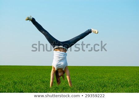 Girl doing a cartwheel in a field Stock photo © IS2