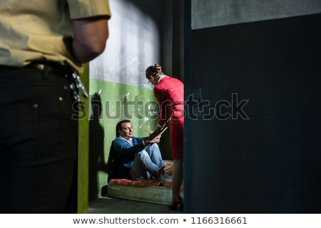 Dedicated female attorney visiting a young inmate in an obsolete prison cell Stock photo © Kzenon