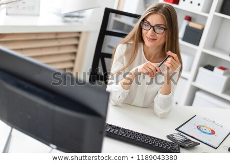 A young girl is sitting at the computer desk in the office, holding a pencil in her hand and working Stock photo © Traimak