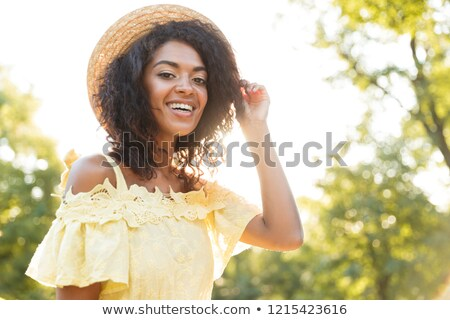 Photo of pretty african american woman 20s wearing straw hat and Stock photo © deandrobot