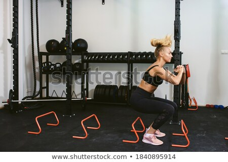 young sports woman jumping make sport exercises isolated indoors stock photo © deandrobot