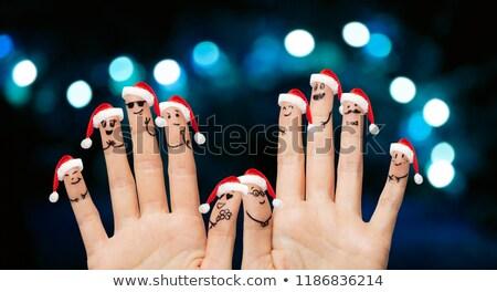 close up of ten fingers in santa hats over lights Stock photo © dolgachov