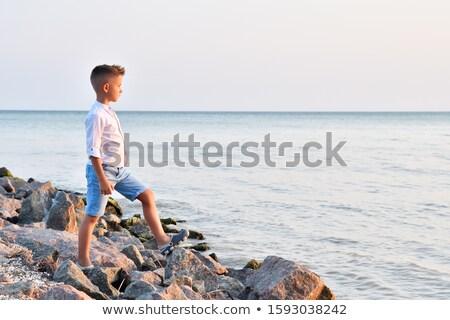 Cute boy stands on the shore watching the ocean waves Stock photo © galitskaya