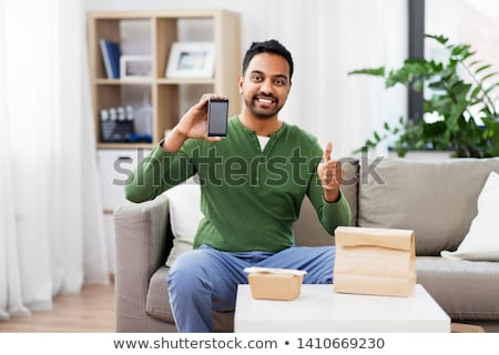 delivery man with food showing thumbs up Stock photo © dolgachov