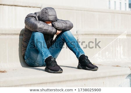 man curled up sitting on an outdoor stairway