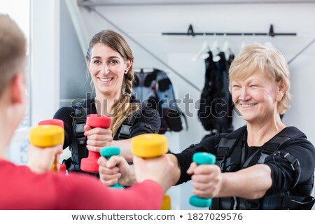 Senior and young woman with dumbbells in wireless ems gym Stock photo © Kzenon