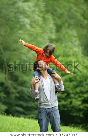 Foto d'archivio: Little Boy Sat On Fathers Shoulders