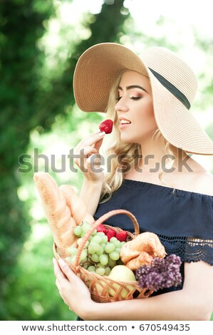 Young beautiful caucasian lady tasting yummy strawberry Stock photo © stockyimages