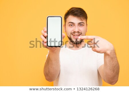 Surprised man pointing to his mobile phone Stock photo © photography33