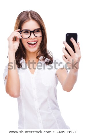Portrait of a beautiful woman on the phone while standing against a white background stock photo © wavebreak_media