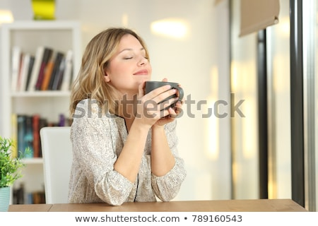 Young woman holding cup of tea or coffee at home and breathing a Stock photo © HASLOO