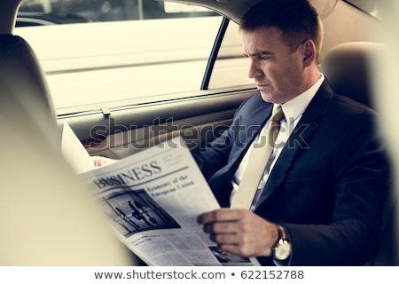 female passenger reading newspaper inside taxi stock photo © stockyimages